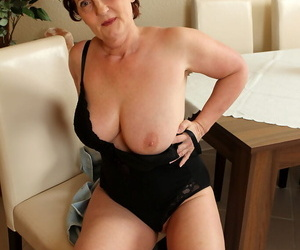 Redheaded oma Hillary G cups her big natural boobs as she disrobes