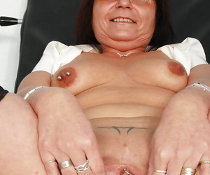 Nasty granny concerning glasses masturbating her muff with an increment of pissing