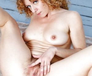 Older hirsute model Leona displaying hairy pits and beaver outdoors