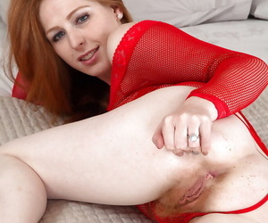 Mature redhead Tia Jones sliding panties aside to display hairy muff