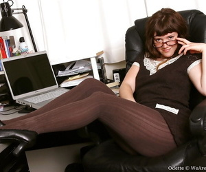 Brunette babe in glasses showing off her fuckable body in the office
