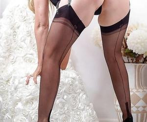 Leggy blonde model in black dress flashing garters and underwear