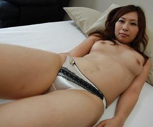 Asian MILF Machiko Nishizaki undressing and exposing her inviting cunt