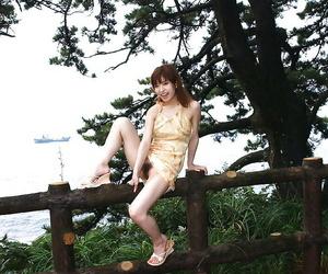 Nasty asian cutie An Nanba slipping off her dress outdoor