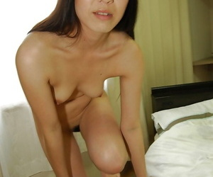 Asian gal in pantyhose undressing and spreading her pussy lips in close up