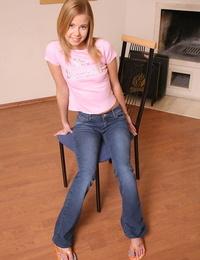 Slim teenage blondie in blue jeans undressing and fingering her gash