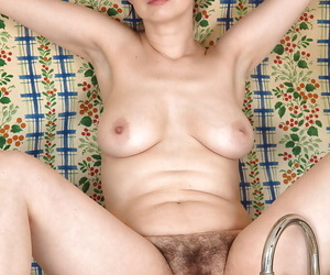 Middle aged lady Nikita pulling down jeans and panties for hairy pussy display