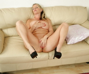 Busty mature lady Jessica doffing skirt and panties to masturbate on sofa
