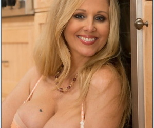 Seductive mature lady with big tits Julia Ann stripping in the kitchen