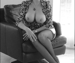 Barely clothed mature brunette in stockings showcases her big round tits