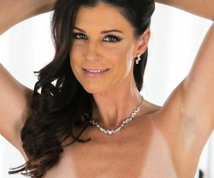 Dark haired American woman India Summer uncovers her tiny tits as she disrobes