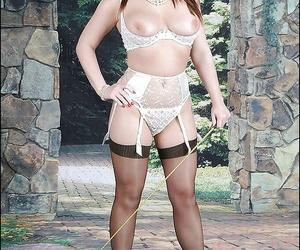 Bosomy mature fetish lady posing in black stockings and white lingerie