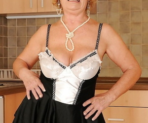 Lubricous granny alongside maid uniform and stockings stripping alongside the kitchen
