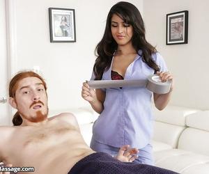 Brunette masseuse Sophia Leone giving handjob to restrained man