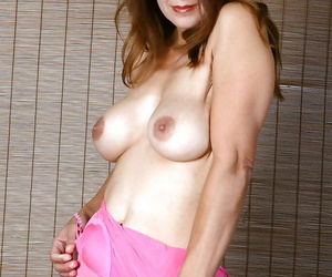 Busty mature posing in pink lingerie and spreading pink pussy