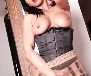 Mature solo model Desyra Noir striking hot poses in corset and nylons