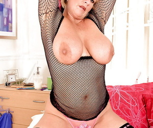 Grown-up blond in fishnet bodystockings exposing her swollen hooters coupled with twat