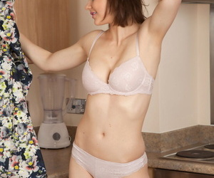 Mature Tina Kay displays her medium boobs while stripping in the kitchen