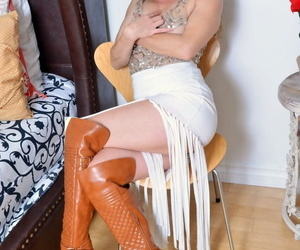 Curly-haired Leona demonstrates unshaved armpits and bushy pussy in sexy boots