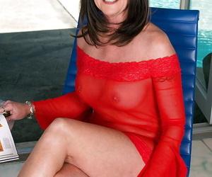 Mature brunette Honey Ray exposing her ass and boobs through sheer red lingerie