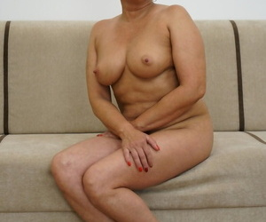 Granny with glasses Jessye showing off her big natural tits on the couch