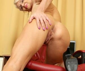 Older secretary Inez crosses her bare legs after disrobing at her desk