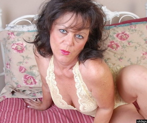 Mature slut Debella strips her white lingerie and stretches her snatch