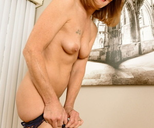 30 plus redhead Cyndi Sinclair doffs 3 piece lingerie and nylons to pose nude