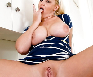 Curvaceous mature blonde revealing her big jugs and teasing her shaved gash