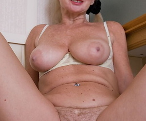 Ugly mature blonde in stockings revealing her massive melons and hairy twat