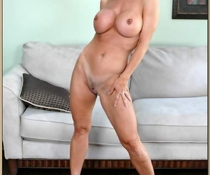Mature blonde Amber Lynn exposing round tits and stripping from panties
