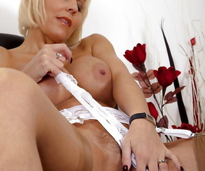 Naughty mature gal in stockings abbreviated the brush knockers together with good-looking pussy