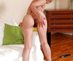 Seductive mature woman with ample ass stripping and spreading her legs