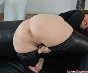 Mature British woman slides down leather pants to expose her sinful cunt