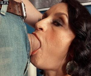 Mature bitch Rita Daniels deepthroats a young lady\'s man and gets cum on fake interior