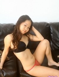 Cute Asian girl strips to her bra and panties on a leather couch