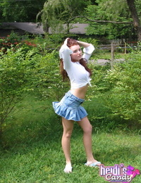 Young amateur model covers her boobs with her hands on the backyard lawn