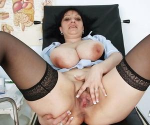 Full-bosomed mature nurse in stockings exposing her twat