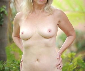 Mature lady Ann Brady heads to the garden to strip to tan stockings
