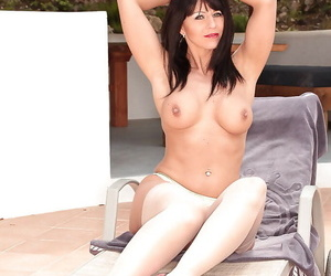 Busty abstruse woman Desyra Noir modeling not at home in sexy nylons