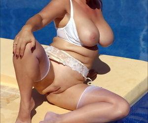 Hot and seductive blonde mature fatty wears sexy white lingerie and stockings in the pool.