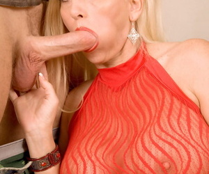 Hugely busty mature MILF in sheer red shirt sucks young cock & rides on top