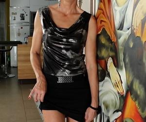 Well-dressed elderly woman slides miniskirt increased by panties down the brush long legs
