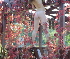 Changeable teen Lara E poses totally unembellished insusceptible to a backyard deck near a river