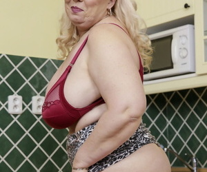 Mature blonde with huge saggy tits masturbates with a toy in stockings