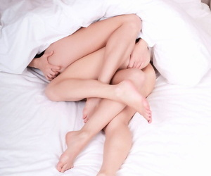 Hot lesbians Kelly G & Piper A entwine their legs while having sex on a bed