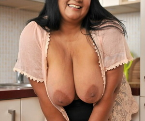 BBW brunette Bubi poses and displays her big natural tits in a kitchen