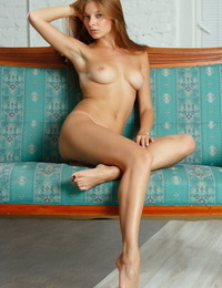 Young redhead with long hair and legs Angelina B disrobes for bare shoot