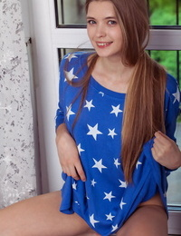 Gorgeous teenage girl with long gams shows off her shaved pussy by a window
