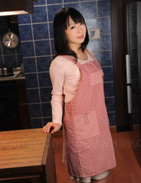 Japanese housewife with a pretty face poses non naked in her kitchen